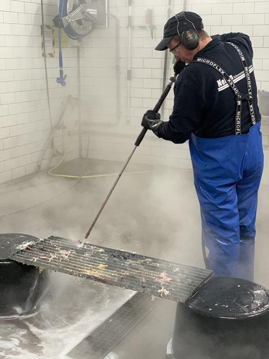 schoonmaker foodbedrijf maakt rooster schoon met hogedrukreiniger