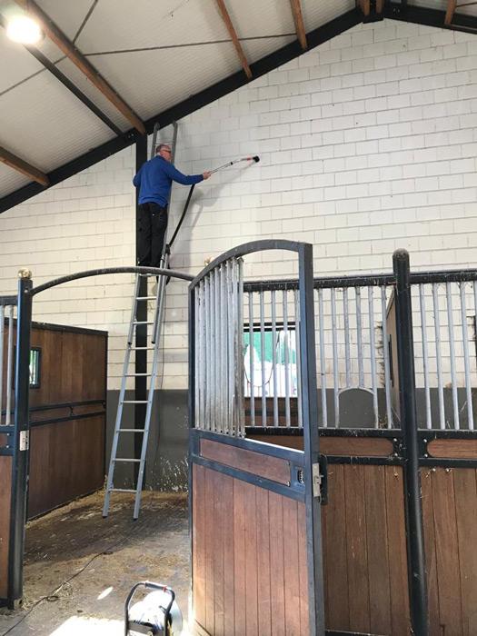 reiniging van een gevel schoonmaker op ladder en waterspuit