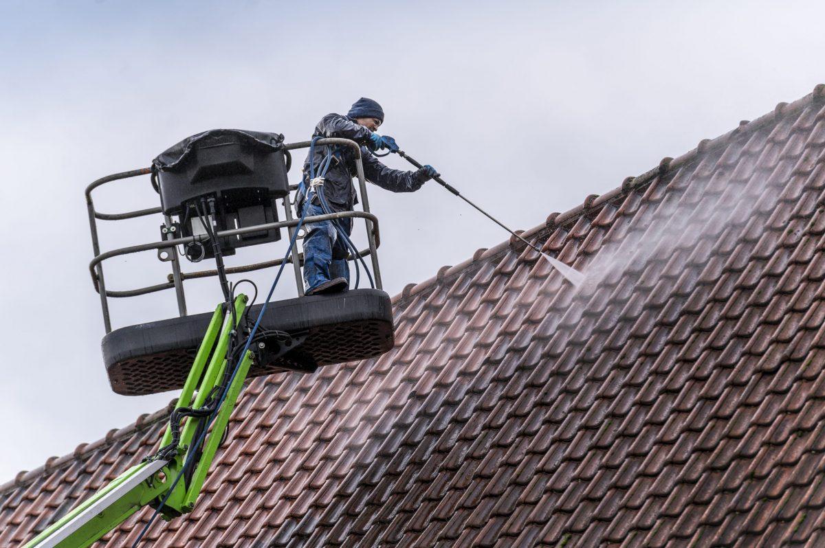 dak schoonmaken met hogedrukreiniger vanaf een hoogwerker