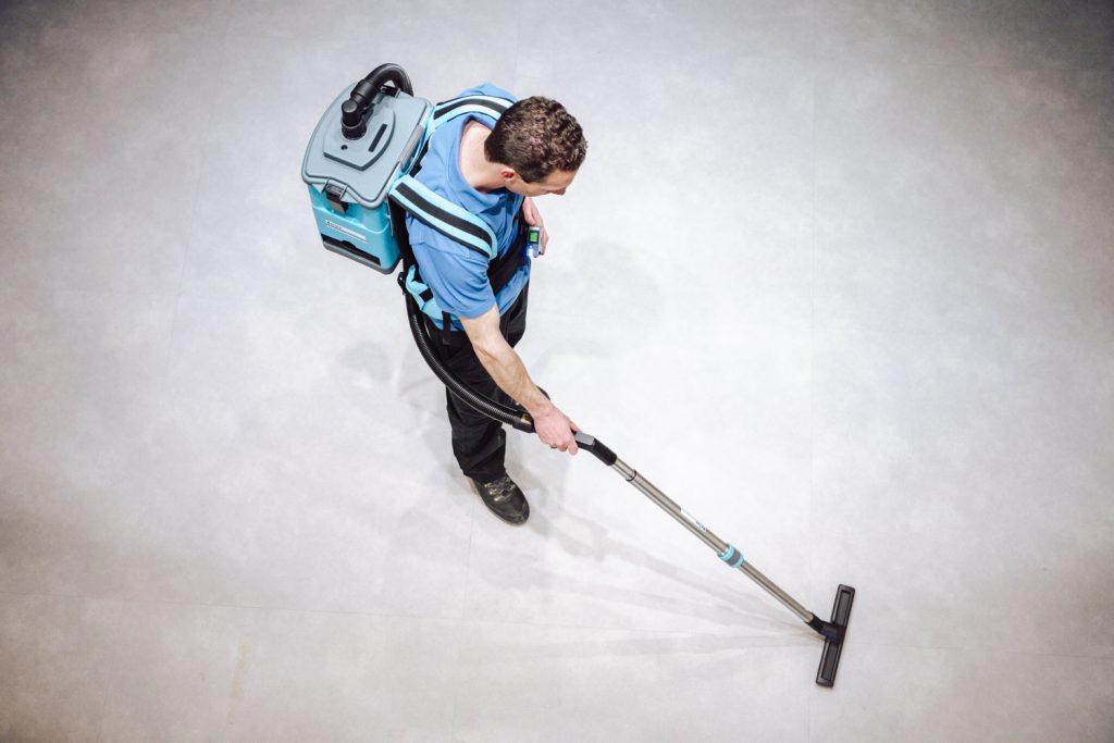 man stofzuigt vloer nellen schoonmaak