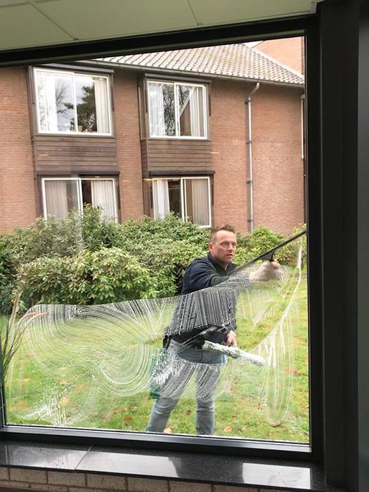 angel nellen maakt een raam schoon bij verzorgingstehuis