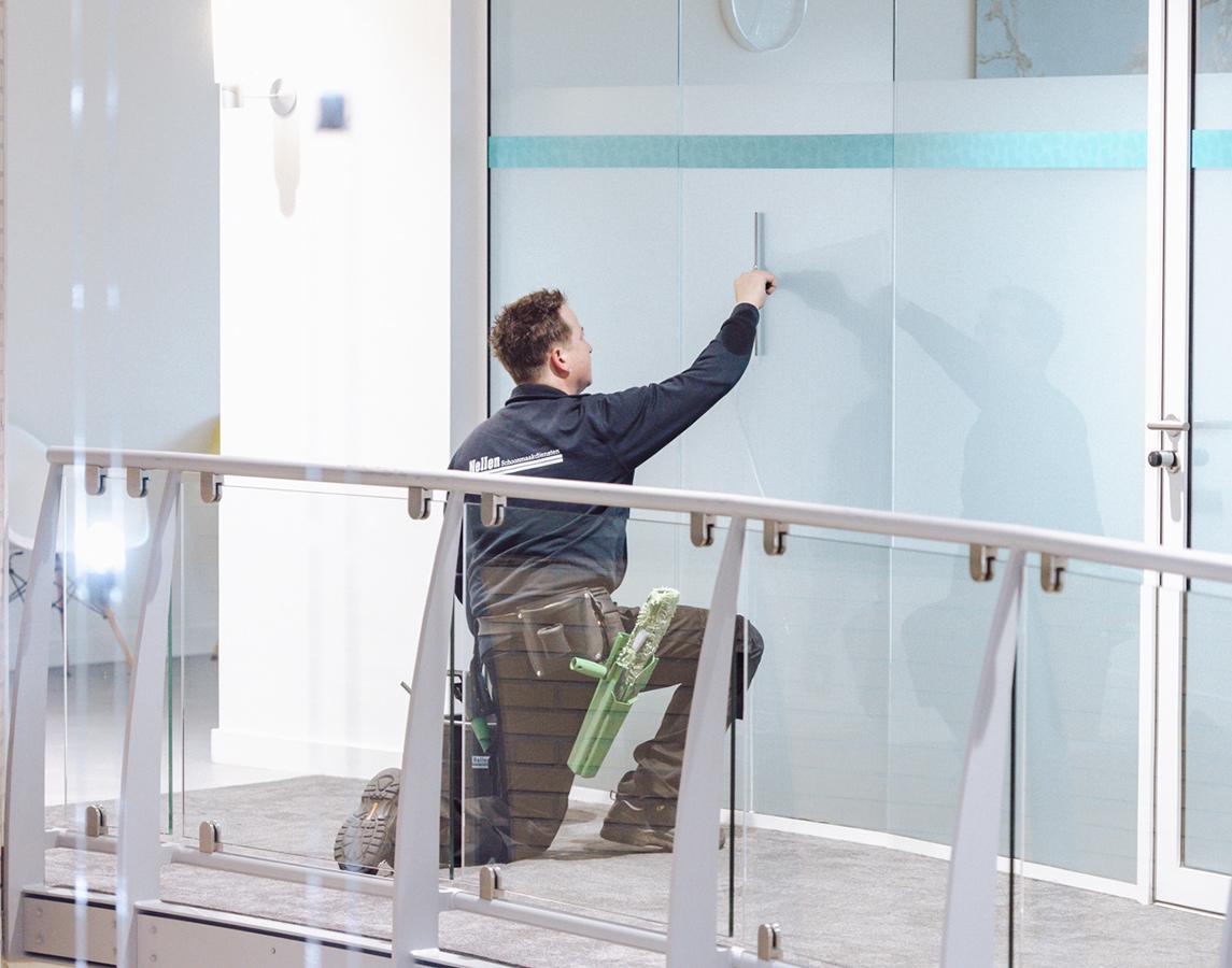 medewerker van nellen wast de ramen van het interieur