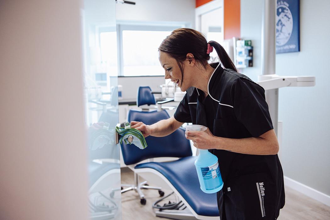 schoonmaakster maakt deur tandarts schoon oss