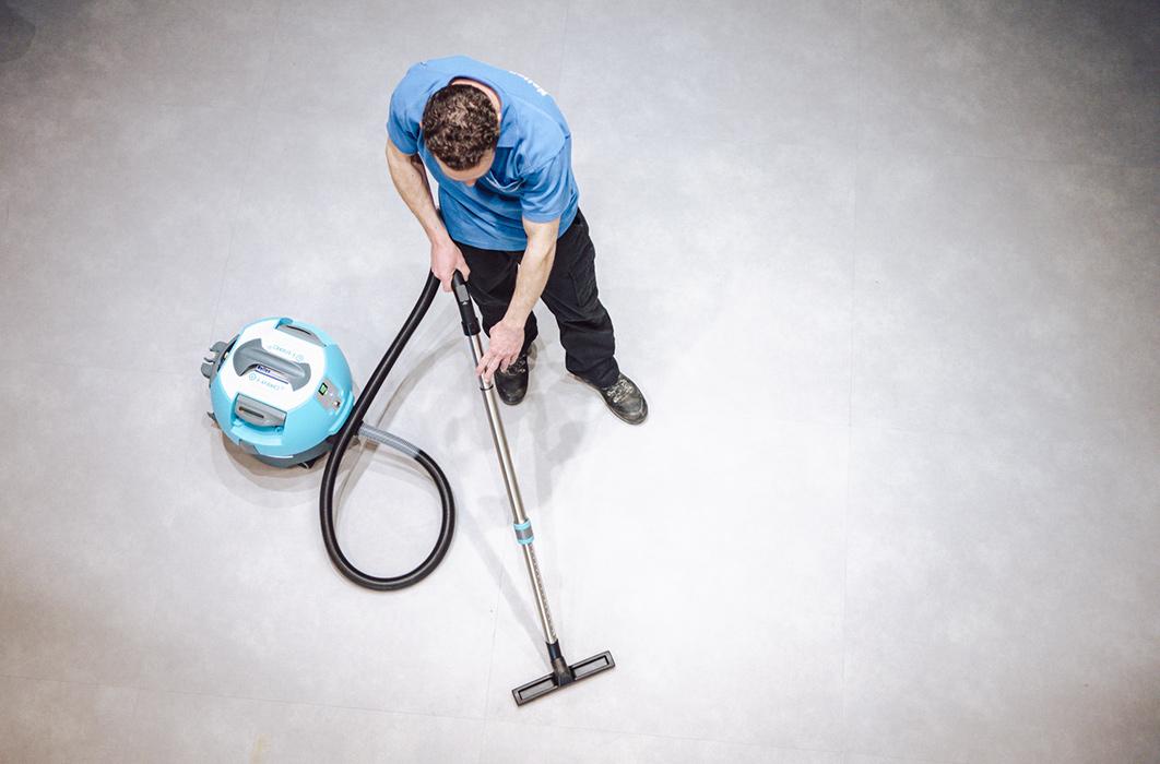 medewerker stofzuigt grote vloer nellen schoonmaak