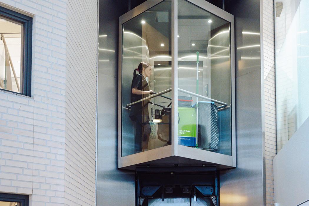 kantoor schoonmaakster in de lift nellen