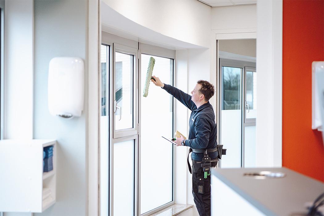 schoonmaker wast een raam bij een tandartspraktijk in oss