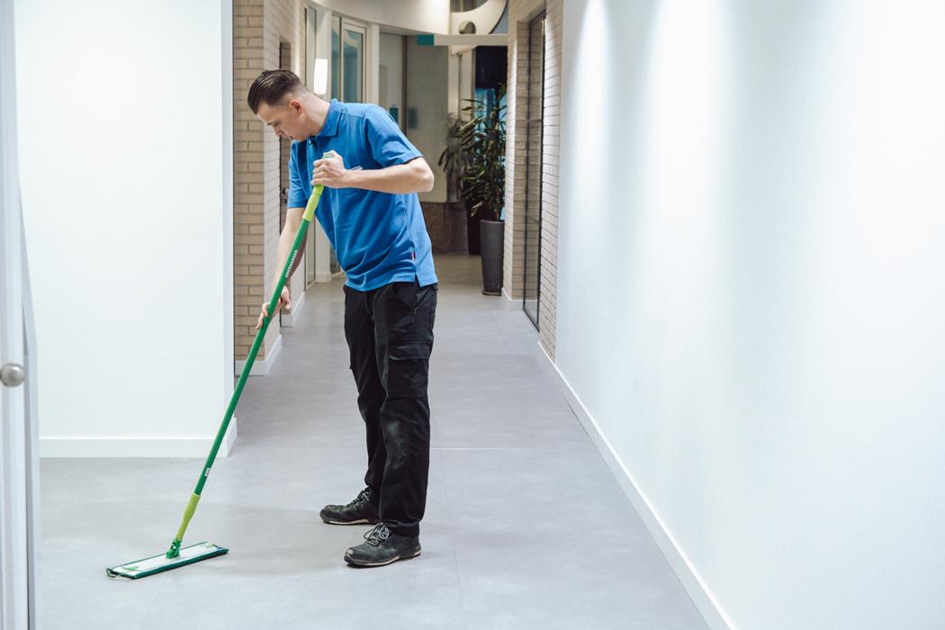 medewerker van nellen dweilt een vloer