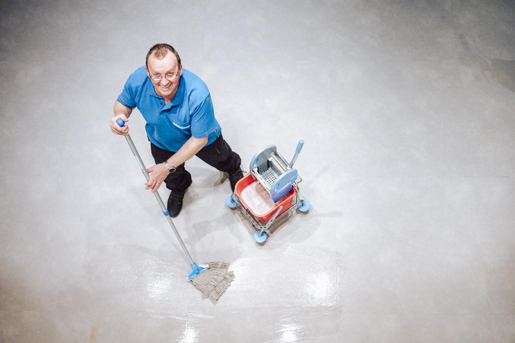 medewerker nellen schoonmaakdiensten dweilt een grote vloer