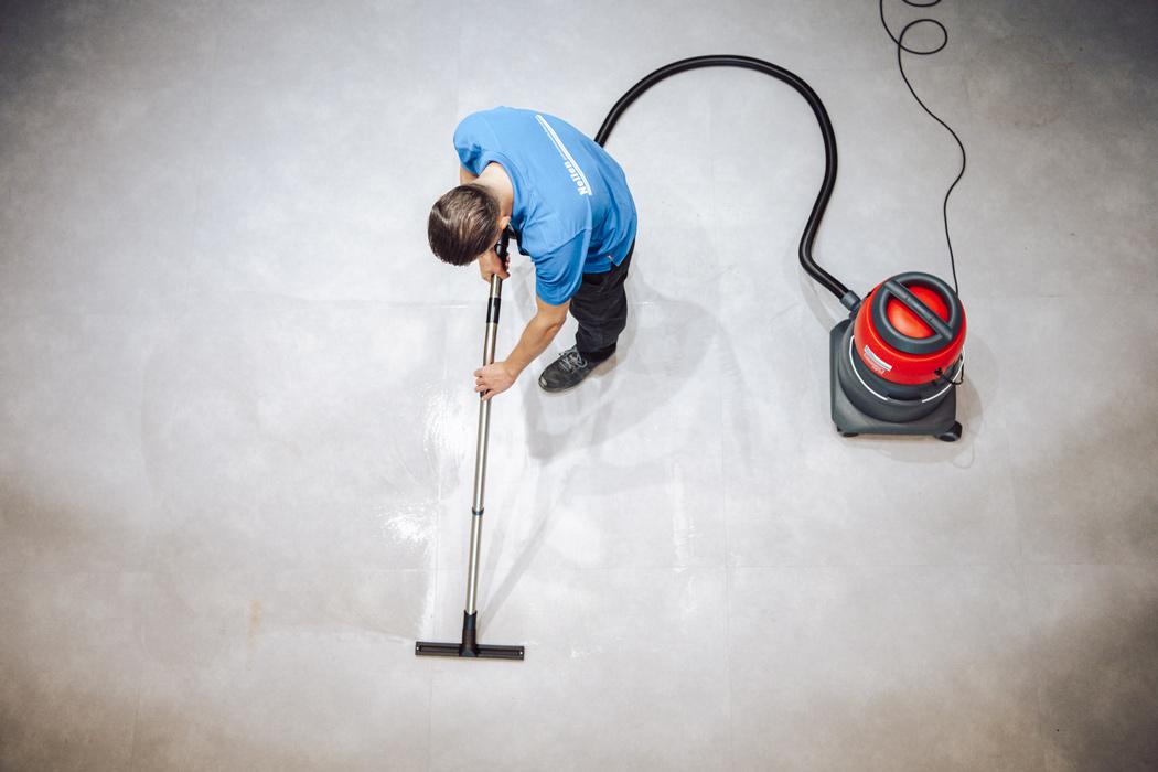 marmoleum schoongemaakt door medewerker van nelen met stofzuiger